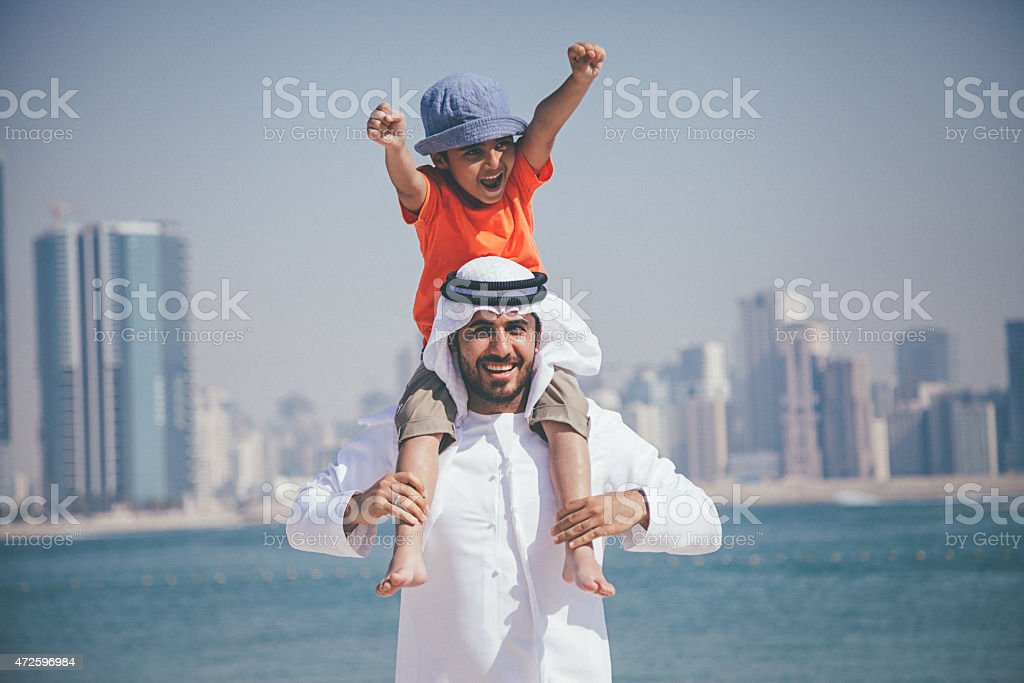 Arab father and son having fun at beach stock photo
