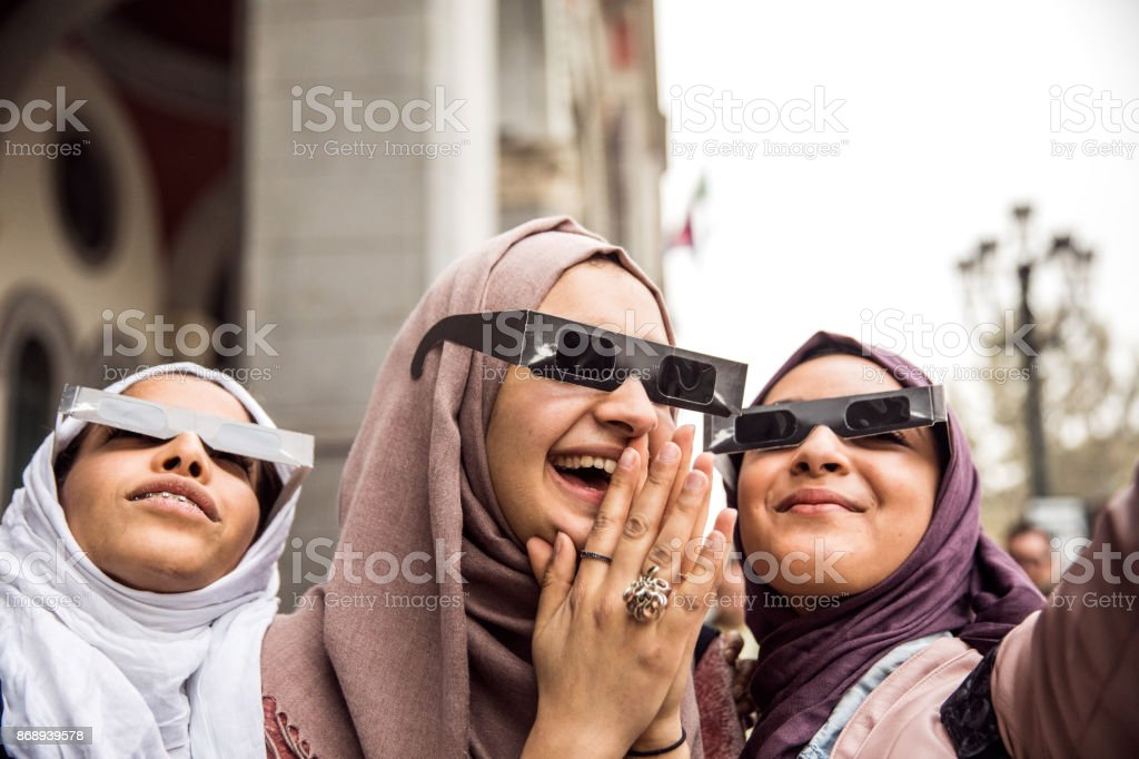Arab friends looking at solar eclipse stock photo