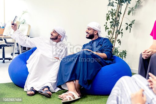 491496340 istock photo Arab friends taking a selfie during casual business discussion 1052937454