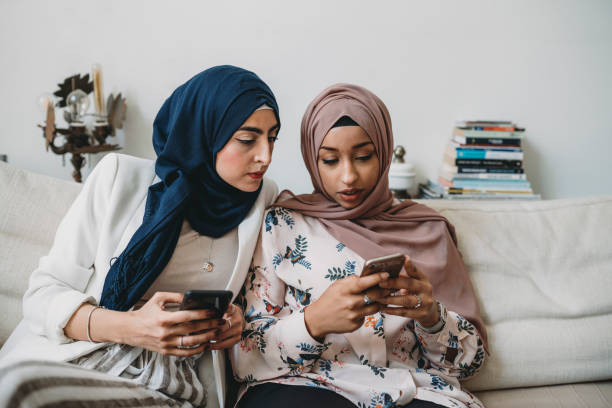 arab friends using mobile phones sitting on the sofa at home - smartphone addiction not groups stock pictures, royalty-free photos & images