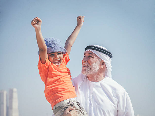 Arab grandfather and little boy having fun at beach stock photo