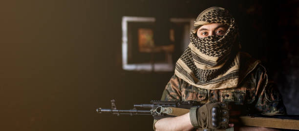Arab male soldier in a headdress from the national keffiyeh with weapons in his hands. Muslim man with guns on black stock photo