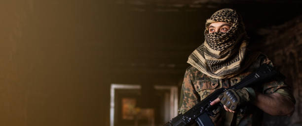 Arab male soldier in a headdress from the national keffiyeh with weapons in his hands. Muslim with firearms stock photo