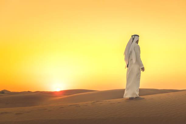 arab man admiring expansive dunes during sunset - arab стоковые фото и изображения