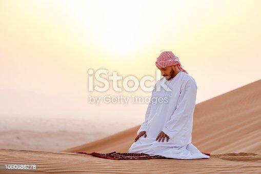 istock Arab man at the dunes praying to Allah 1050686278