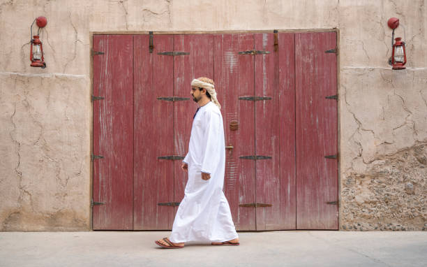 Arab Man in traditional clothing walking in Al Seef, the newly built old area of Dubai stock photo