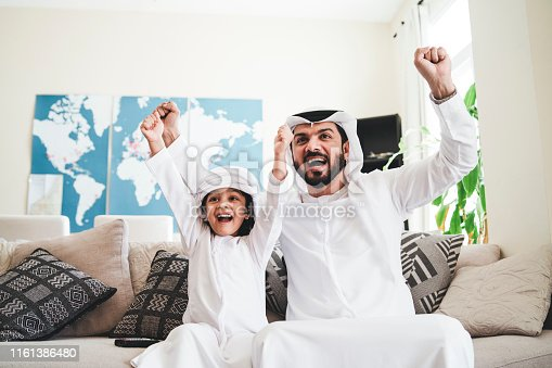 istock Arab man looking TV at home during a sport event with his son 1161386480