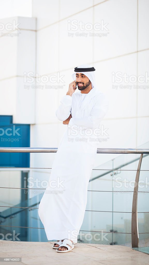 Young Emirati entrepreneur is talking on phone with clients and...