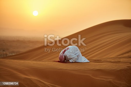 Arab man praying on mat in desert. Male is in traditional wear. He is kneeling on sand.