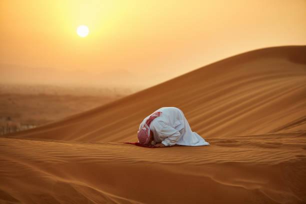 Arab man praying on carpet in desert during sunset stock photo