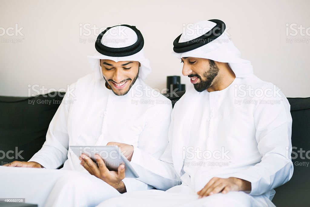 Arab Man Showing Something to His Friend on a Tablet stock photo
