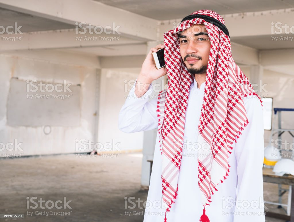 Arab man smiling and using smart phone while working in construction site. Copy space. royalty-free stock photo