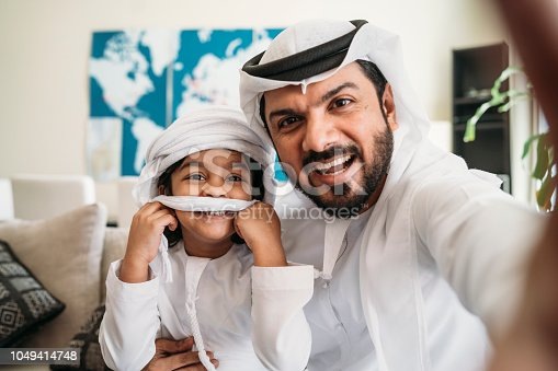491496340 istock photo Arab man taking a selfie with his son on the sofa at home 1049414748