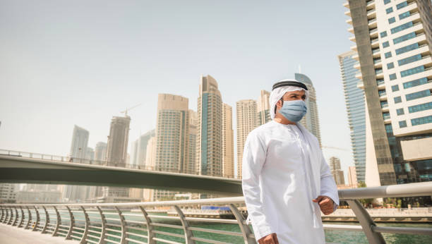 arab man walking in Dubai with face mask stock photo