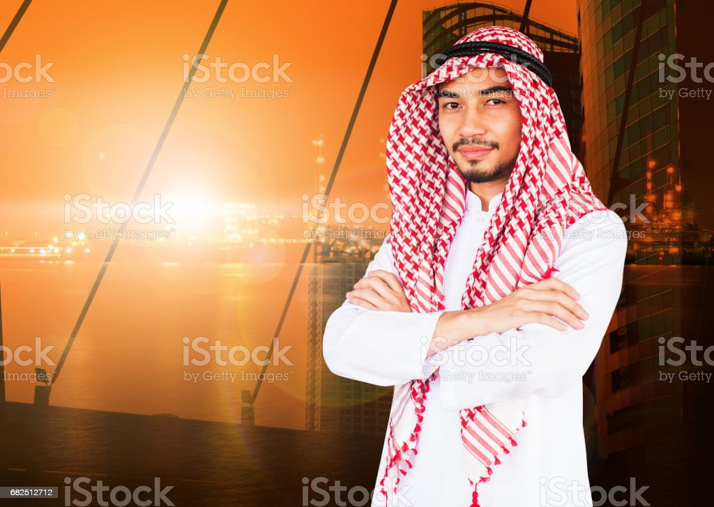Arab man with arms crossed feeling happy, success concept, double exposure photo of city view and oil refinery background. Copy space. royalty-free stock photo