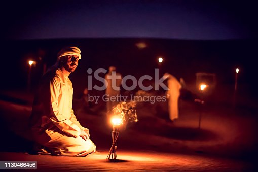 istock Arab Mean Seated on the Sand Dunes Near an Oil Lamp at a Camp Site 1130466456
