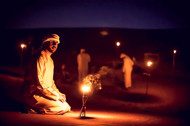 Arab Mean Seated on the Sand Dunes Near an Oil Lamp at a Camp Site stock photo