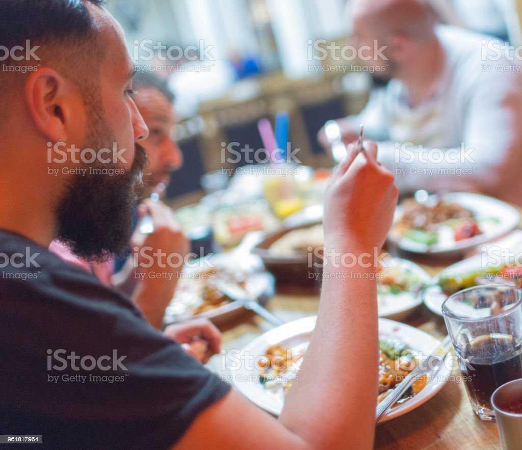 Arab men in restaurant enjoying Middle Eastern food royalty-free stock photo