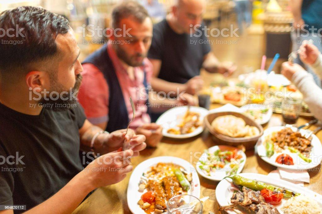 Arab men in restaurant enjoying Middle Eastern food royalty-free stock photo