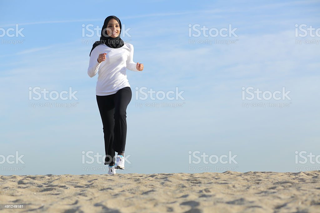 Arab saudi emirates woman running on the beach stock photo