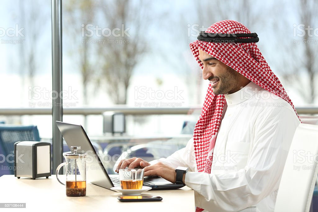 Arab saudi man working online with a laptop stock photo