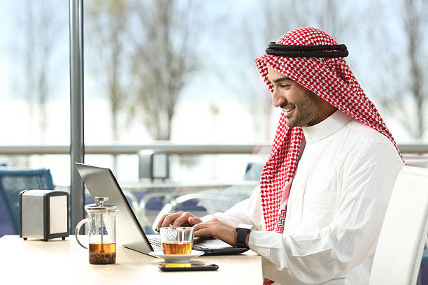 Arab saudi man working online with a laptop Arab saudi man working online with a laptop and smartwatch in a coffee shop or an hotel bar with a window and outdoor terrace in the background saudi arabia stock pictures, royalty-free photos & images