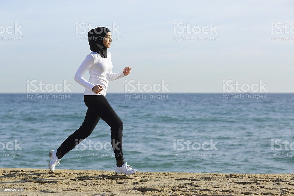 Arab saudi runner woman running on the beach stock photo