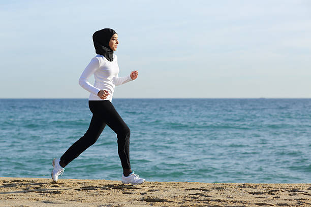 arab saudi runner woman running on the beach - arabic girl stock photos and pictures