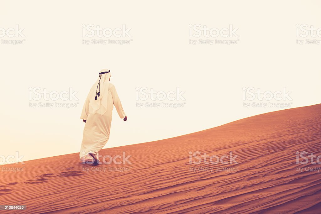 Arab walking alone on the sand dunes stock photo