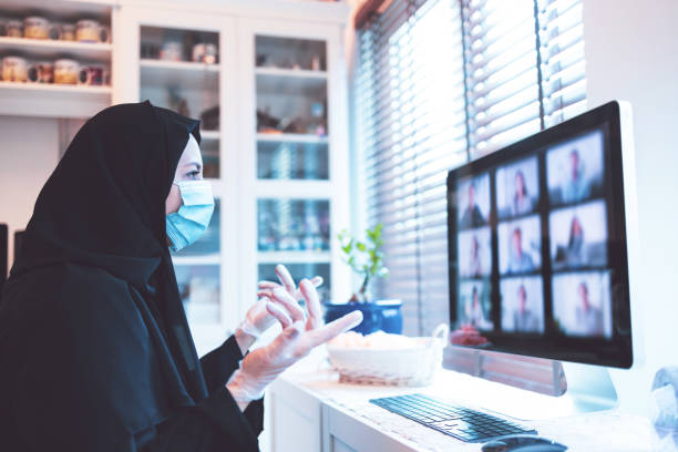 Arab woman attending video call while working from home - COVID-19 Series stock photo