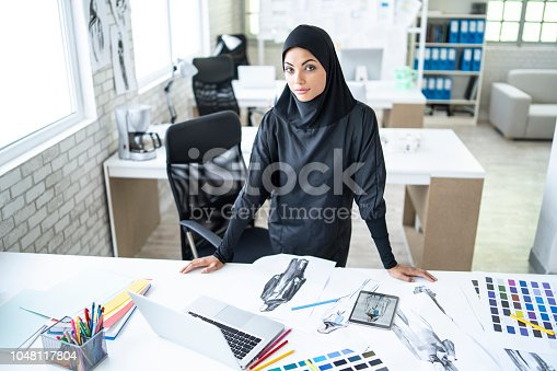 Arab woman fashion designer standing in studio, looking at camera.