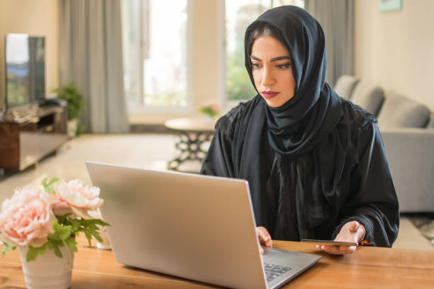 Arab woman in hijab using laptop and smart phone at home stock photo