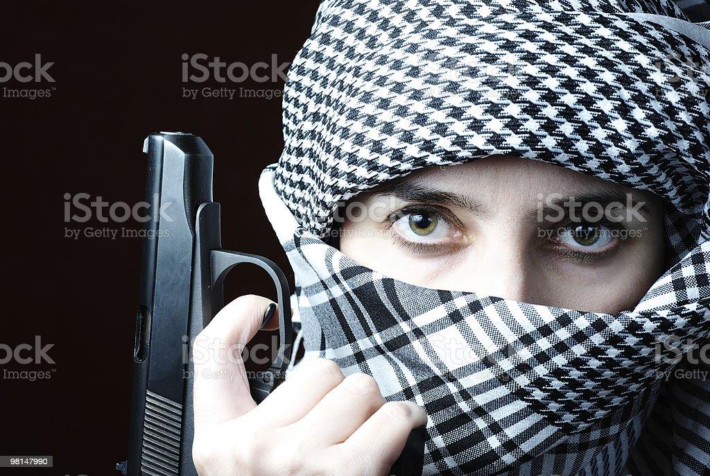Arab woman in keffiyeh with gun royalty-free stock photo