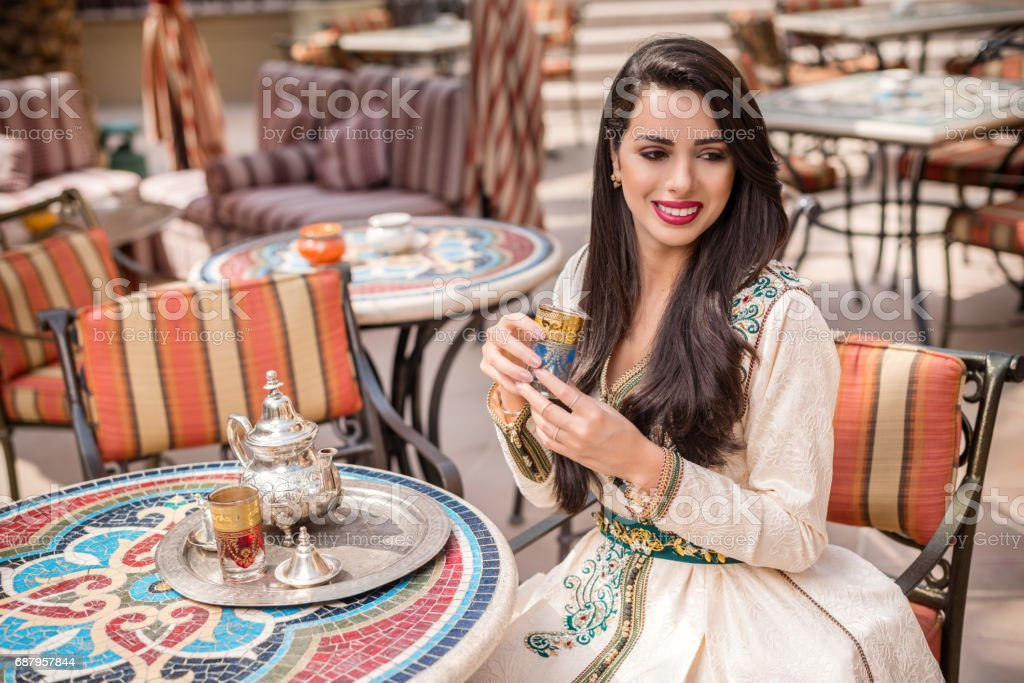 Arab Woman in national dress holding tea cup. Middle Eastern arab woman in traditional  Moroccan dress drinking Moroccan Tea. Ramadan holiday theme. stock photo