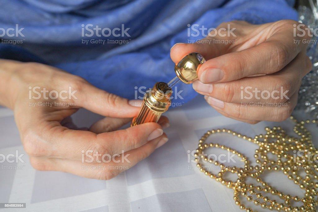Arab woman opening perfume bottle. stock photo