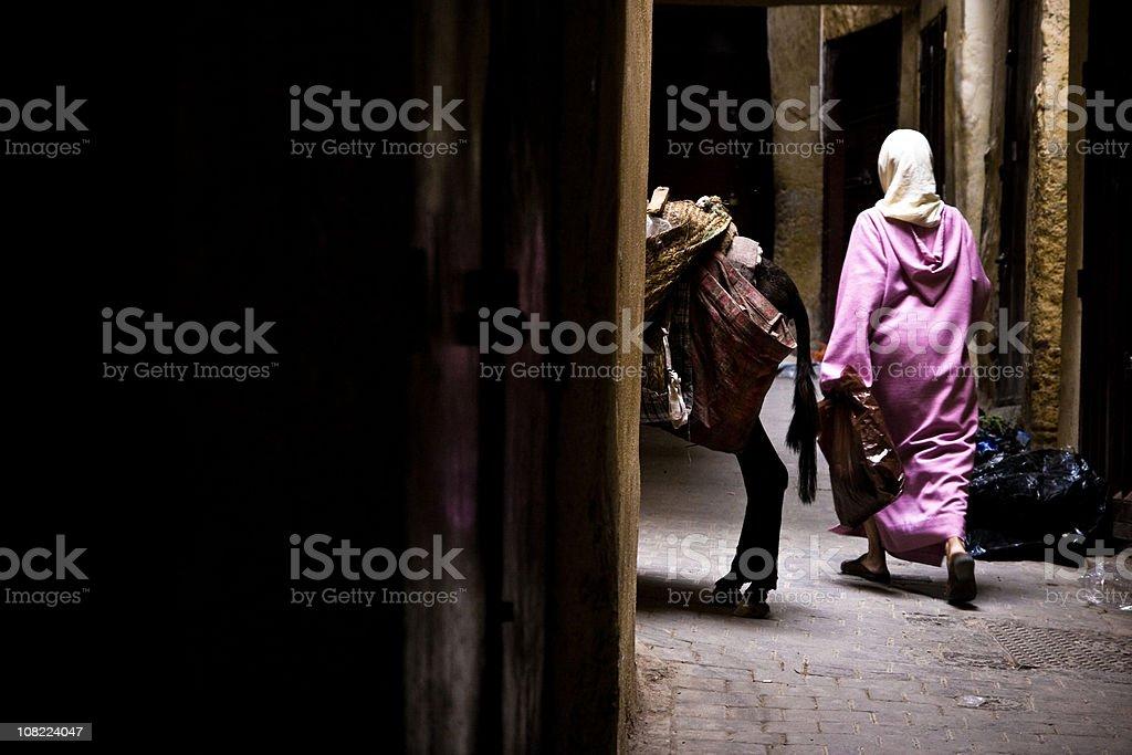 Arab woman walking in a narrow street stock photo