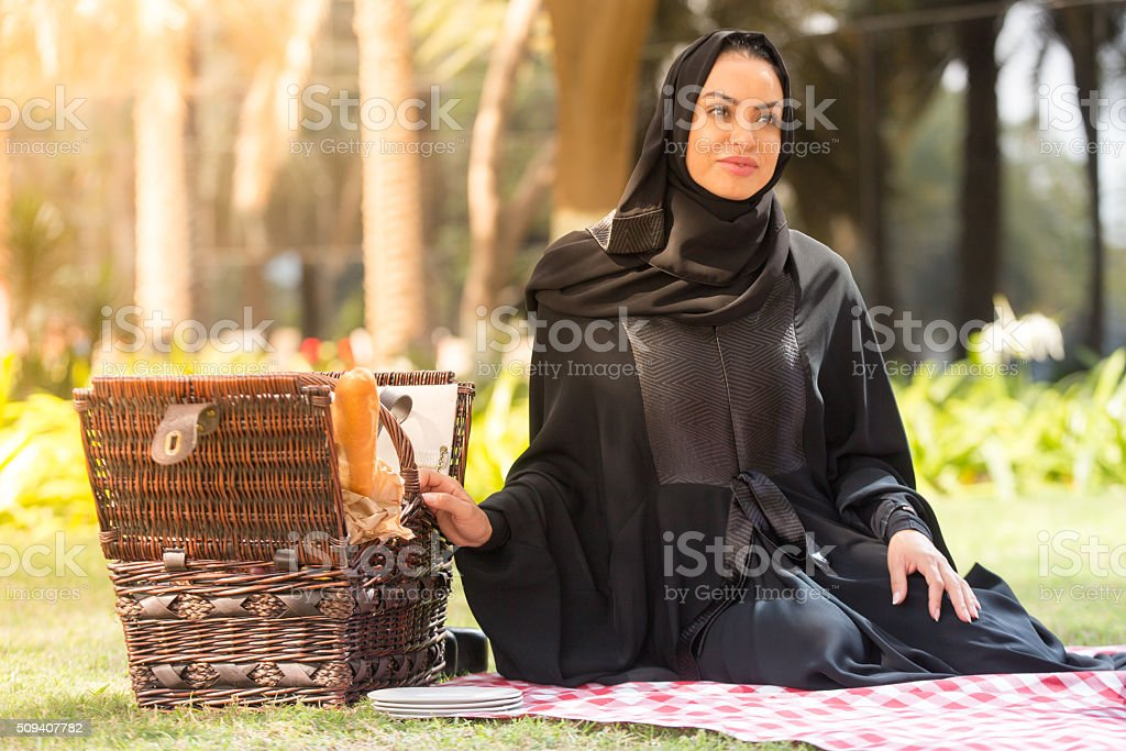 Arab woman with a picnic basket in a park, Dubai stock photo