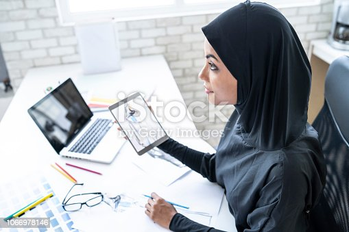 Female designer working in studio, using laptop and digital tablet.