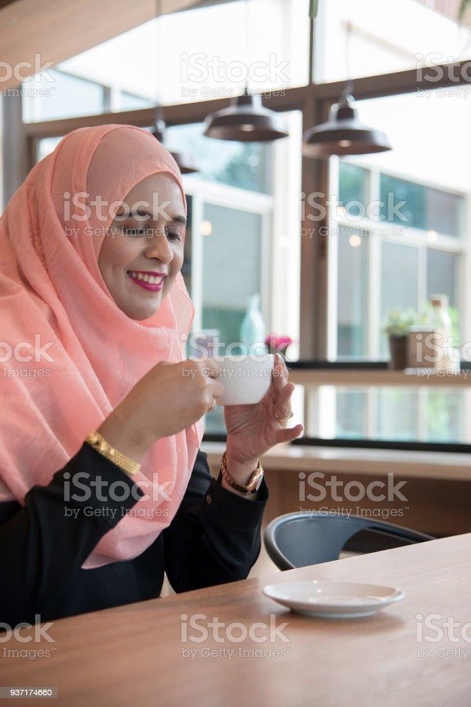 Mujeres árabes en hijab sosteniendo y taza de café sentado en la cafetería. - foto de stock