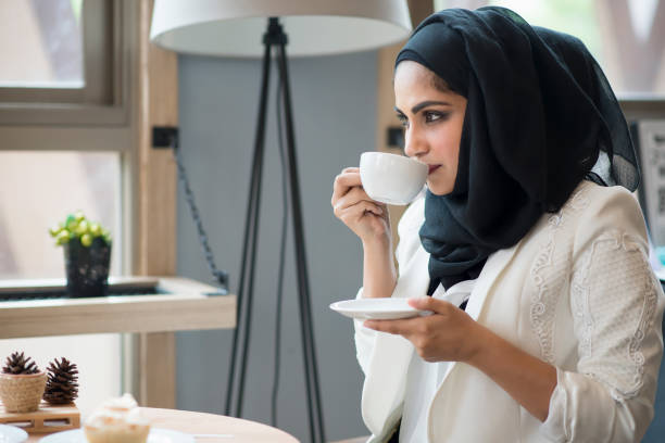 arab women in hijab holding and drinking coffee cup sitting in the coffee shop. - saudi woman stock photos and pictures
