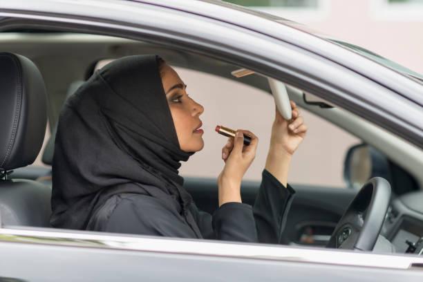 Mujeres árabes utilizando maquillaje en coche. - foto de stock
