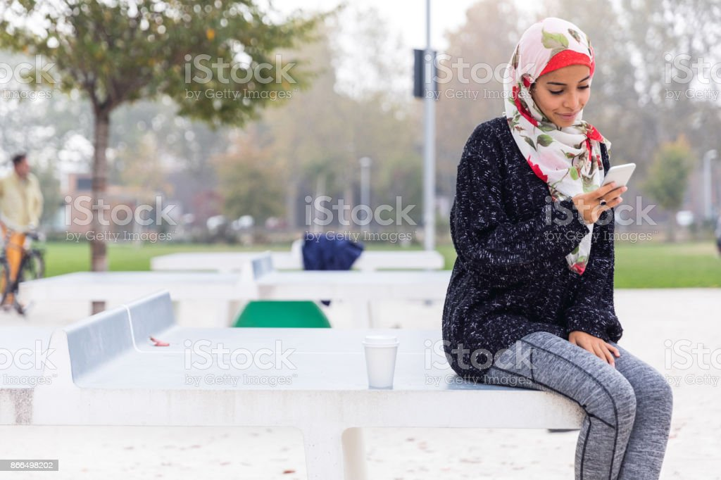 Arab Youth - Millennial texting on mobile while waiting for a friend at the public park stock photo
