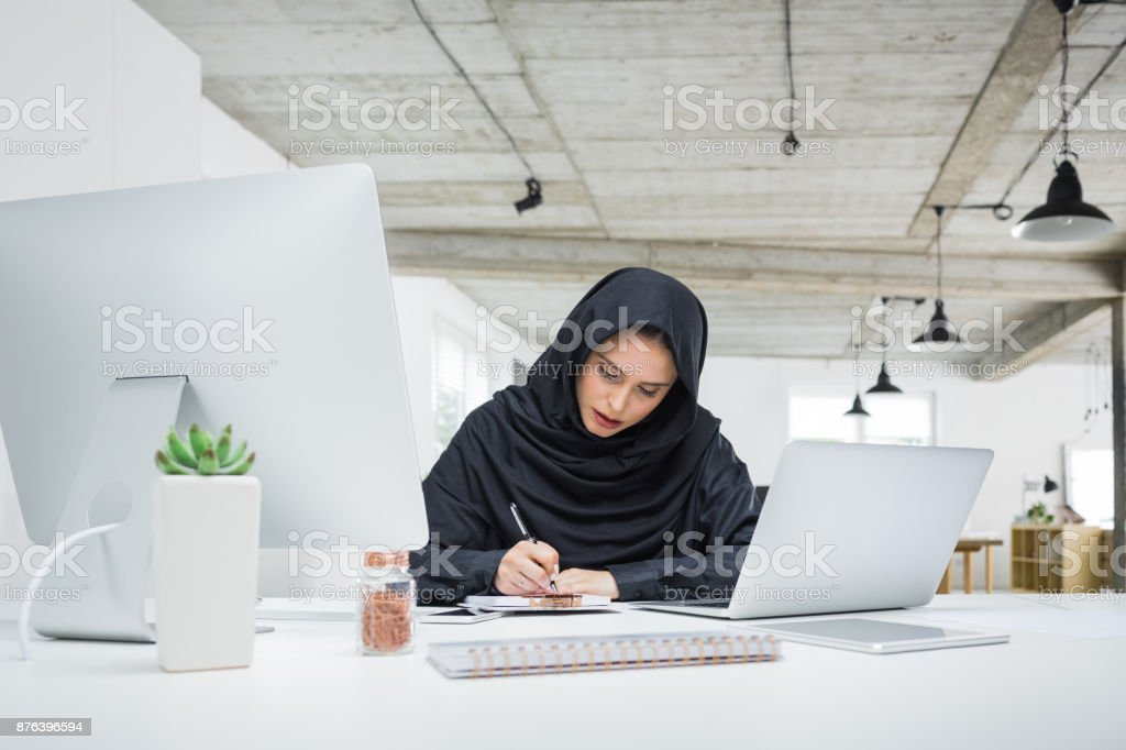 Arabia business woman working in office Arabia business woman working in office. Female sitting at her desk with laptop computer and writing notes on notepad. Adult Stock Photo