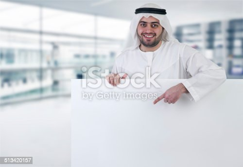 istock arabian business man pointing at a blank white sign 513420157