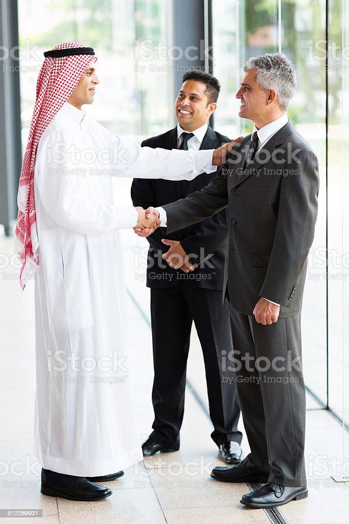 arabian businessman greeting business partners stock photo