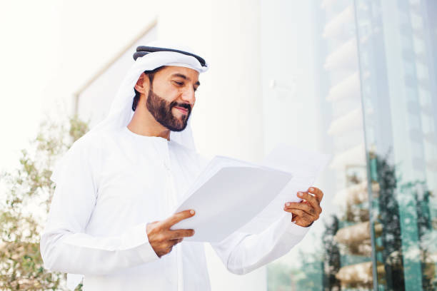 Arabian businessman Middle eastern businessman in kandora looking at documents arabia stock pictures, royalty-free photos & images