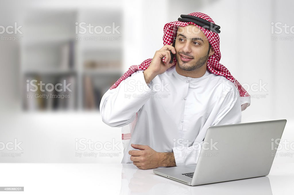 Arabian businessman with laptop and speaking on his phone stock photo