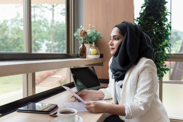 arabian businesswoman working in the coffee shop. - хиджаб стоковые фото и изображения