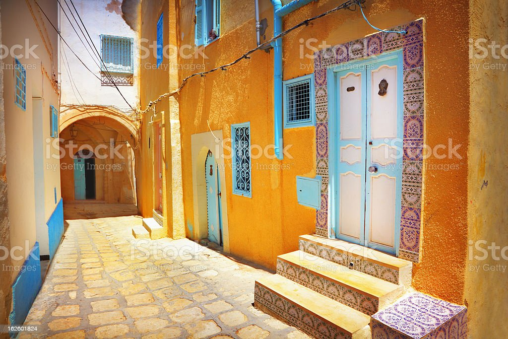 Arabian cobblestone street with orange colored building stock photo