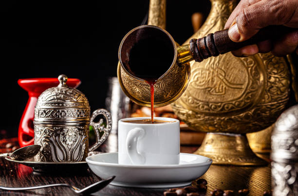 Arabian cuisine. Black coffee is poured from the Turks into a cup. Serving coffee in an Arabian restaurant. Background image. copy space